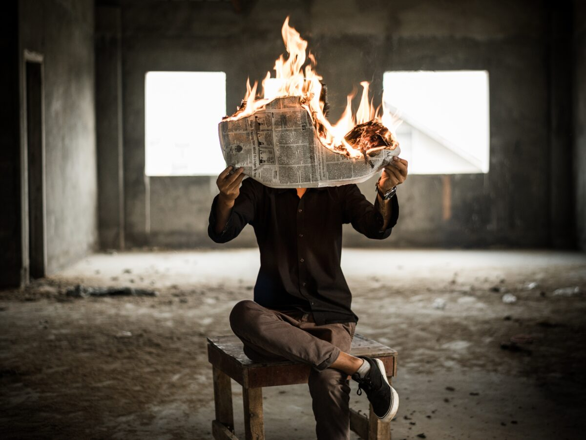 istinite laži - man sitting on chair holding newspaper on fire