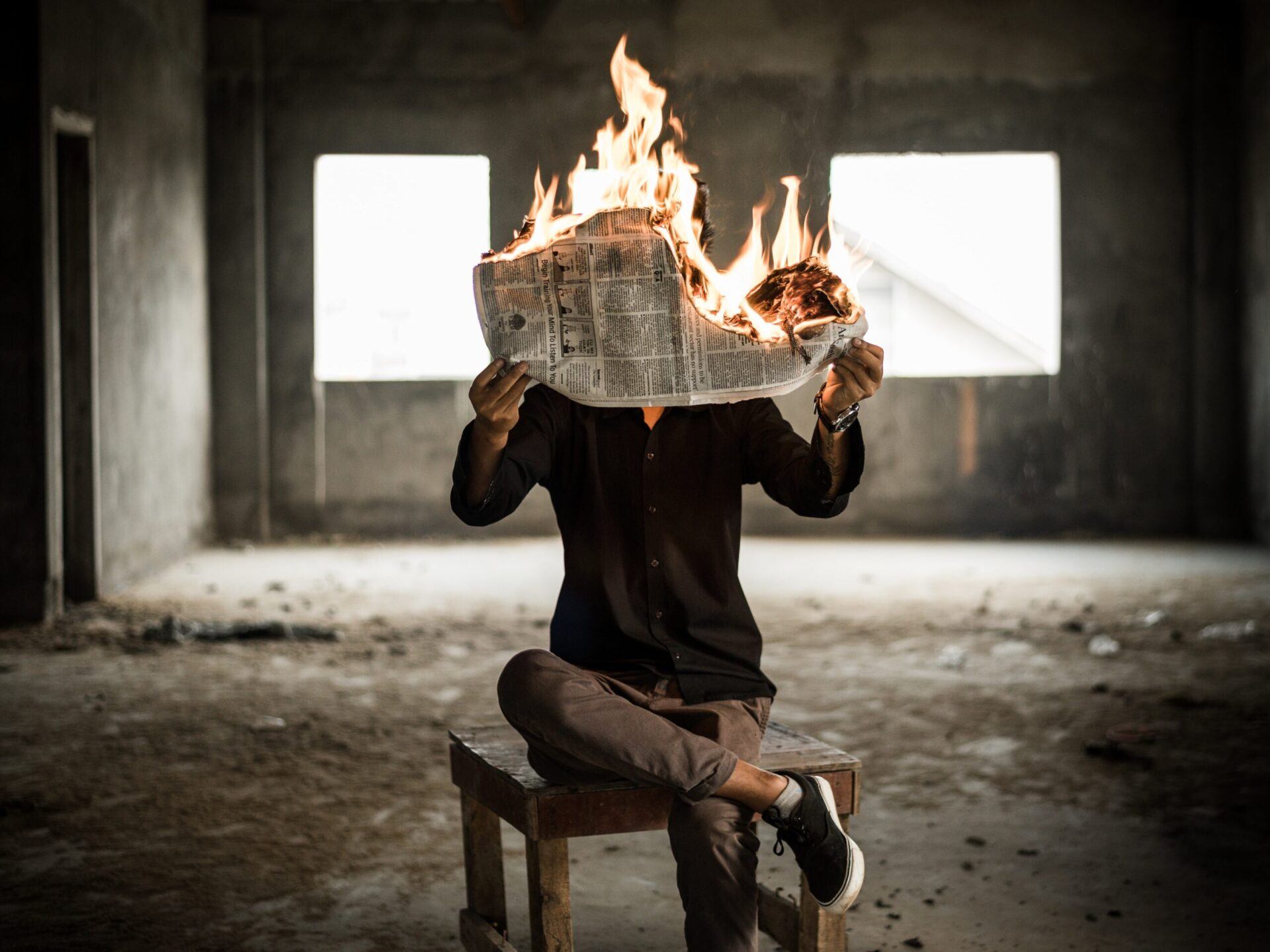 istinite laži - man sitting on chair holding newspaper on fire