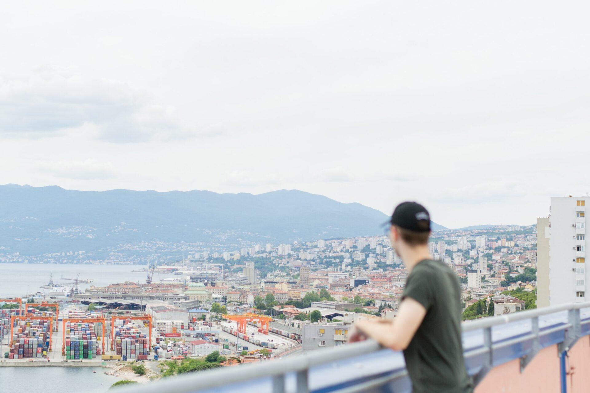 man standing on railing overlooking city buildings