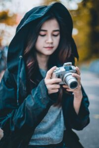 woman in blue jacket holding black and silver camera